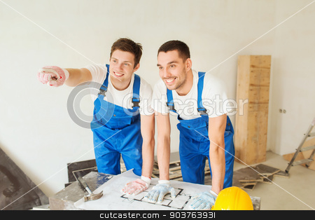 smiling builders with blueprint stock photo, building, teamwork and people concept - smiling builders in hardhats with blueprint pointing finger indoors by Syda Productions