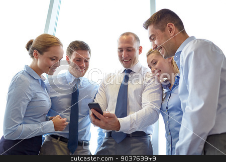 happy businesspeople with smartphone stock photo, business, teamwork, people and technology concept - business team looking to smartphone in office by Syda Productions