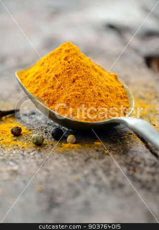 Ground turmeric stock photo, Ground turmeric in a spoon  by sutike