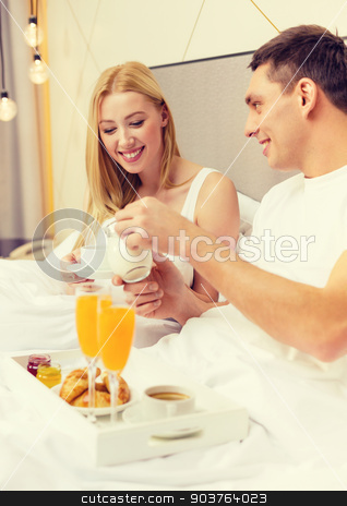 smiling couple having breakfast in bed in hotel stock photo, hotel, travel, relationships and happiness concept - smiling couple having breakfast in bed in hotel room by Syda Productions