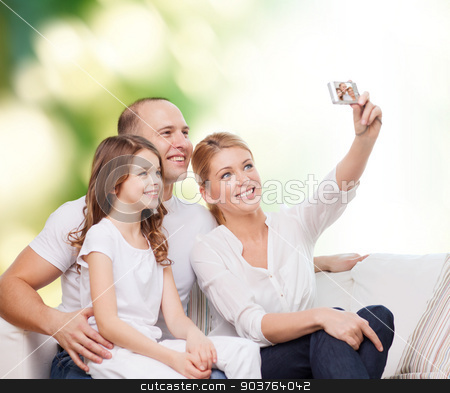 happy family with camera at home stock photo, family, technology, ecology and people concept - smiling mother, father and little girl making selfie with camera over green background by Syda Productions