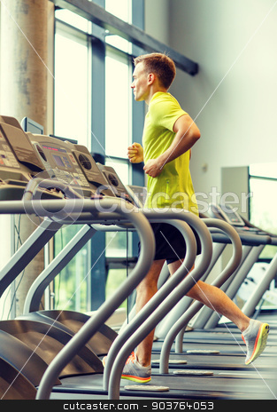 smiling man exercising on treadmill in gym stock photo, sport, fitness, lifestyle, technology and people concept - smiling man exercising on treadmill in gym by Syda Productions