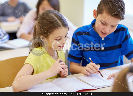 group of school kids writing test in classroom stock photo, education, elementary school, learning and people concept - group of school kids with pens and notebooks writing test in classroom by Syda Productions