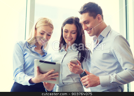 business team working with tablet pcs in office stock photo, business and office concept - smiling business team working with tablet pcs and smartphones in office by Syda Productions