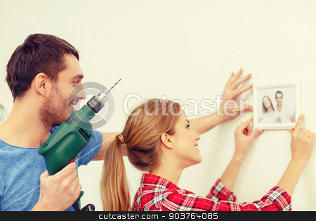 smiling couple drilling hole in wall at home stock photo, repair, interior design, building, renovation and home concept - smiling couple drilling hole in wall and putting picture up at home by Syda Productions