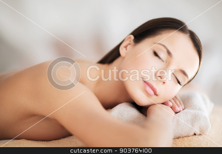 beautiful woman with closed eyes in spa stock photo, health and beauty, resort and relaxation concept - beautiful woman with closed eyes in spa salon lying on the massage desk by Syda Productions