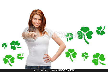 smiling girl in white t-shirt pointing at you stock photo, gestures, holidays, st. patricks day and people concept - happy teenager in blank white t-shirt pointing at you over white background with green shamrock or clover by Syda Productions
