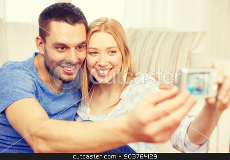 smiling couple taking picture with digital camera stock photo, love, family, technology and happiness concept - smiling couple taking self portrait picture with digital camera at home by Syda Productions