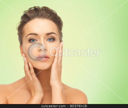 beautiful young woman face stock photo, beauty, people and health concept - beautiful young woman touching her face over green background by Syda Productions