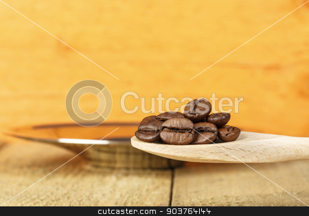 Coffee beans in a wooden spoon stock photo, Coffee beans in a wooden spoon over silver plate by marekusz