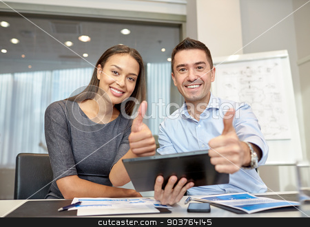 smiling businesspeople with tablet pc in office stock photo, business, people, technology and teamwork concept - smiling businessman and businesswoman with tablet pc computer showing thumbs up gesture meeting in office by Syda Productions
