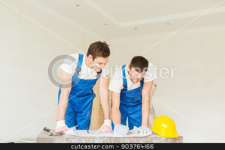 group of builders with blueprint stock photo, business, building, teamwork and people concept - group of smiling builders with blueprint and hardhat indoors by Syda Productions