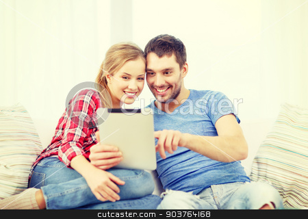 smiling couple with tablet pc computer at home stock photo, home, technology and relationships concept - smiling couple with tablet pc computer at home by Syda Productions