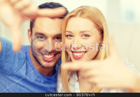 smiling happy couple making frame gesture at home stock photo, love, family and happiness concept - smiling happy couple making frame gesture at home by Syda Productions