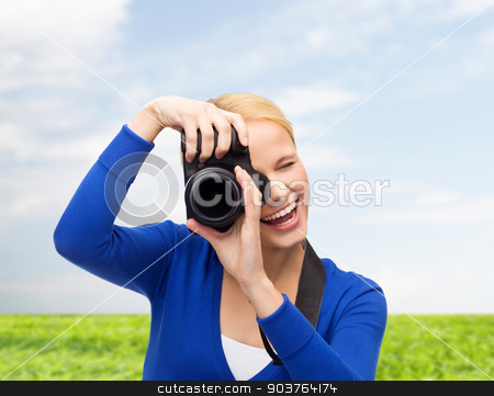 smiling woman taking picture with digital camera stock photo, photography, technology, summer and people concept - smiling young woman taking picture with digital camera over blue sky and grass background by Syda Productions