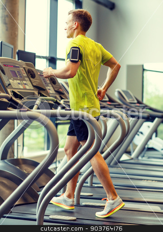 man with smartphone exercising on treadmill in gym stock photo, sport, fitness, lifestyle, technology and people concept - man with smartphone and earphones exercising on treadmill in gym by Syda Productions