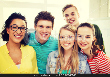 group of smiling people at school or home stock photo, education and happiness concept - group of young smiling people at home or school by Syda Productions