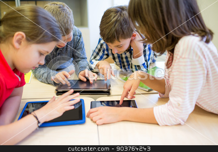 group of school kids with tablet pc in classroom stock photo, education, elementary school, learning, technology and people concept - group of school kids with tablet pc computer having fun on break in classroom by Syda Productions