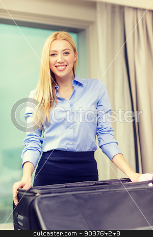 businesswoman packing things in suitcase stock photo, business, technology, internet and hotel concept - happy businesswoman packing things in suitcase in hotel room by Syda Productions