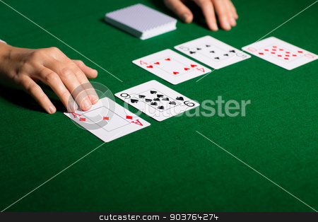 holdem dealer with playing cards stock photo, casino, gambling, poker, people and entertainment concept - close up of holdem dealer hands with playing cards by Syda Productions