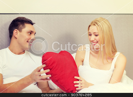 smiling couple in bed with red heart shape pillow stock photo, hotel, travel, relationships, holidays and happiness concept - smiling couple in bed with red heart-shaped pillow by Syda Productions