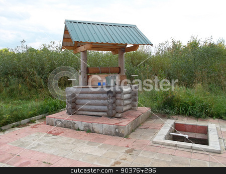 Well in the Russian village stock photo, Well made of wooden logs in the Russian village amid tall grass. by IgorTravkin