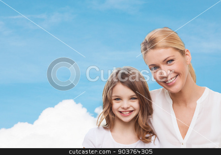 smiling mother and little girl stock photo, family, childhood, happiness and people - smiling mother and little girl over blue sky and white cloud background by Syda Productions