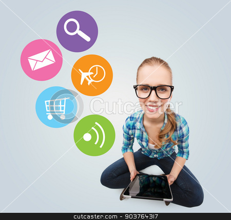 smiling teen girl sitting on floor with tablet pc stock photo, communication, technology, internet and people concept - smiling teenage girl in eyeglasses sitting on floor and holding tablet pc computer over gray background with colorful icons by Syda Productions