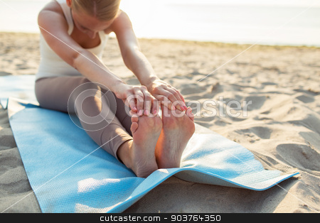 close up of woman making yoga exercises outdoors stock photo, fitness, sport, people and lifestyle concept - close up of woman making yoga exercises on mat outdoors by Syda Productions