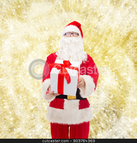 man in costume of santa claus with gift box stock photo, christmas, holidays and people concept - man in costume of santa claus with gift box over yellow lights background by Syda Productions