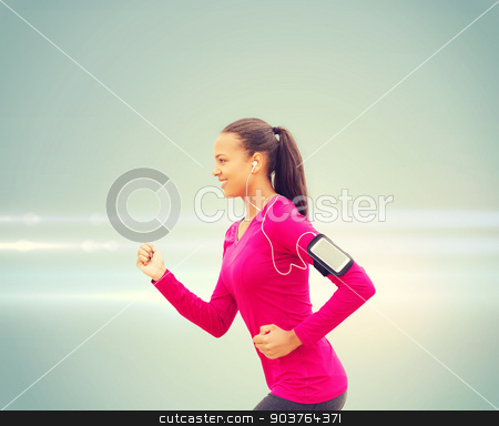 smiling young woman running stock photo, sport, fitness, health, technology and people concept - smiling young african american woman running with smartphone and earphones by Syda Productions