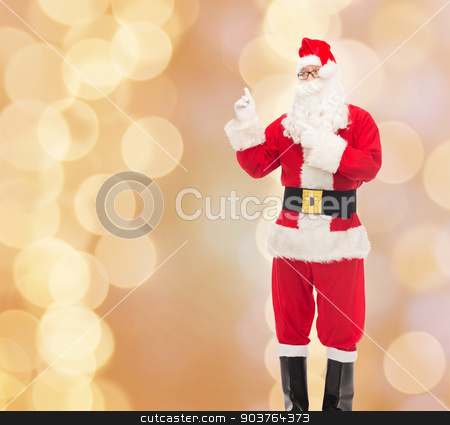man in costume of santa claus stock photo, christmas, holidays, gesture and people concept - man in costume of santa claus pointing fingers over beige lights background by Syda Productions