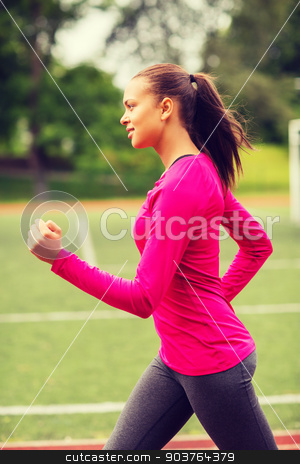 smiling woman running on track outdoors stock photo, fitness, sport, training and lifestyle concept - smiling african american woman running on track outdoors by Syda Productions