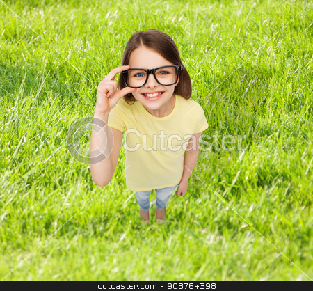 smiling little girl in black eyeglasses stock photo, education, school, people, childhood and vision concept - smiling little girl in black eyeglasses over grass background by Syda Productions