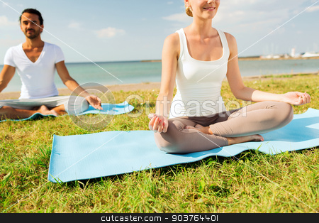 close up of smiling couple making yoga exercises stock photo, fitness, sport, people and lifestyle concept - close up of smiling couple making yoga exercises sitting on mats outdoors by Syda Productions
