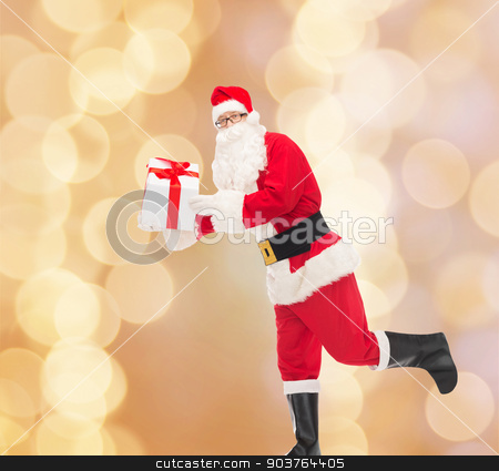 man in costume of santa claus with gift box stock photo, christmas, holidays and people concept - man in costume of santa claus running with gift box over beige lights background by Syda Productions