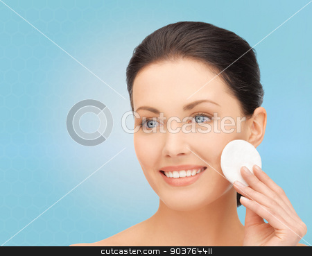 smiling woman cleaning face skin with cotton pad stock photo, beauty, people and health concept - beautiful smiling woman cleaning face skin with cotton pad over blue background by Syda Productions