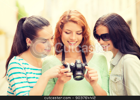 smiling teenage girls with camera stock photo, tourism, travel, leisure, holidays and friendship concept - smiling teenage girls with camera outdoors by Syda Productions