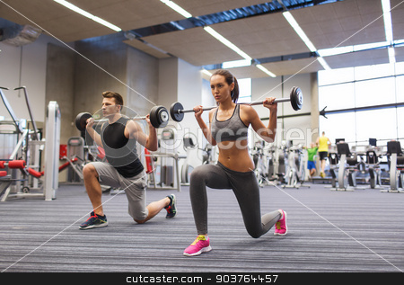 young man and woman training with barbell in gym stock photo, sport, bodybuilding, lifestyle and people concept - young man and woman with barbell flexing muscles and making shoulder press lunge in gym by Syda Productions