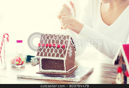 close up of woman making gingerbread house at home stock photo, cooking, people, christmas and decoration concept - close up of woman making gingerbread houses at home by Syda Productions