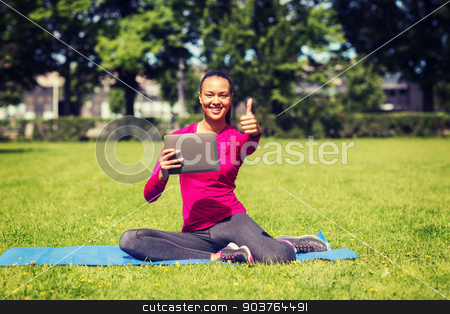 smiling woman with tablet pc showing thumbs up stock photo, fitness, park, technology, gesture and people concept - smiling african american woman with tablet pc showing thumbs up outdoors by Syda Productions