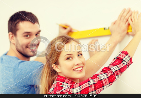 couple building using spirit level to measure stock photo, repair, building and home concept - smiling couple building new home using spirit level to measure by Syda Productions