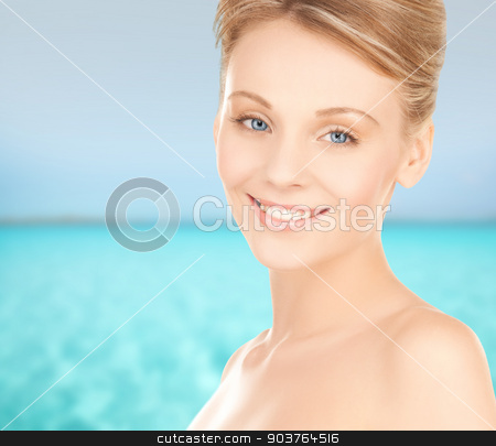 beautiful young woman face stock photo, beauty, people and health concept - beautiful young woman face over blue sea and sky background by Syda Productions