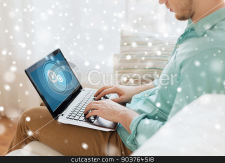 close up of man working with laptop at home stock photo, technology, leisure, people and lifestyle concept - close up of man working with laptop computer and sitting on sofa at home by Syda Productions