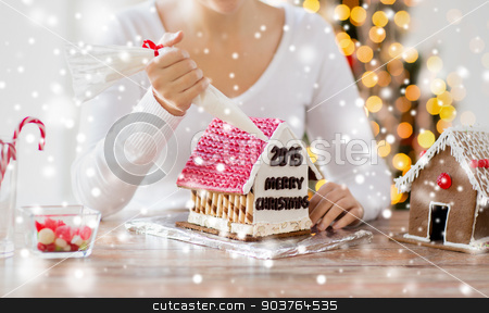 close up of woman making gingerbread houses stock photo, cooking, people, christmas and decoration concept - happy woman making gingerbread houses at home by Syda Productions