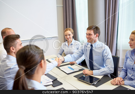 group of smiling business people meeting in office stock photo, business, people, partnership, gesture and startup concept - group of smiling business people meeting and shaking hands in office by Syda Productions