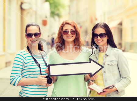 smiling teenage girls with white arrow outdoors stock photo, tourism, travel, vacation, direction and friendship concept - smiling teenage girls with white arrow showing direction outdoors by Syda Productions