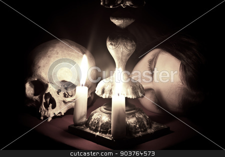 Waiting stock photo, The head of a young girl lying beside to the skull and candlestick. Shutter speed 30 sec by Suchota