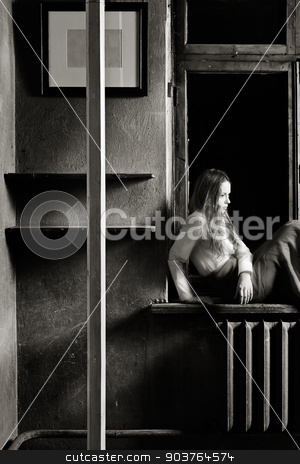 corners stock photo, young girl sitting on the windowsill in the gloomy place. toned black and white.  by Suchota