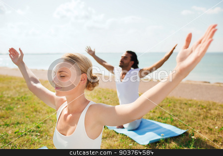 smiling couple making yoga exercises outdoors stock photo, fitness, sport, friendship and lifestyle concept - smiling couple making yoga exercises sitting on mats outdoors by Syda Productions